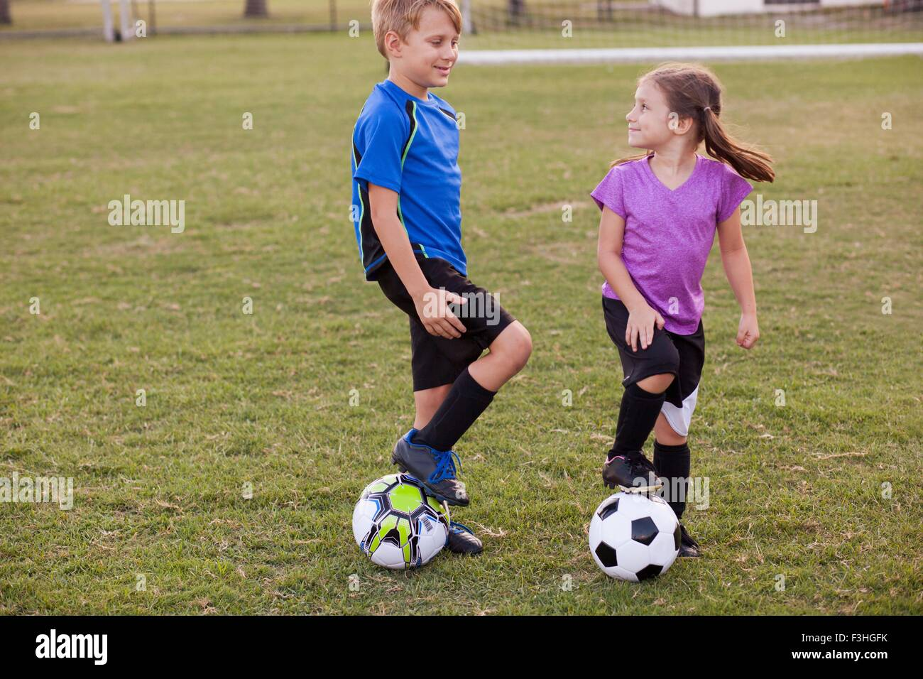 Boy and younger sister with footballs on practice pitch - Stock Image