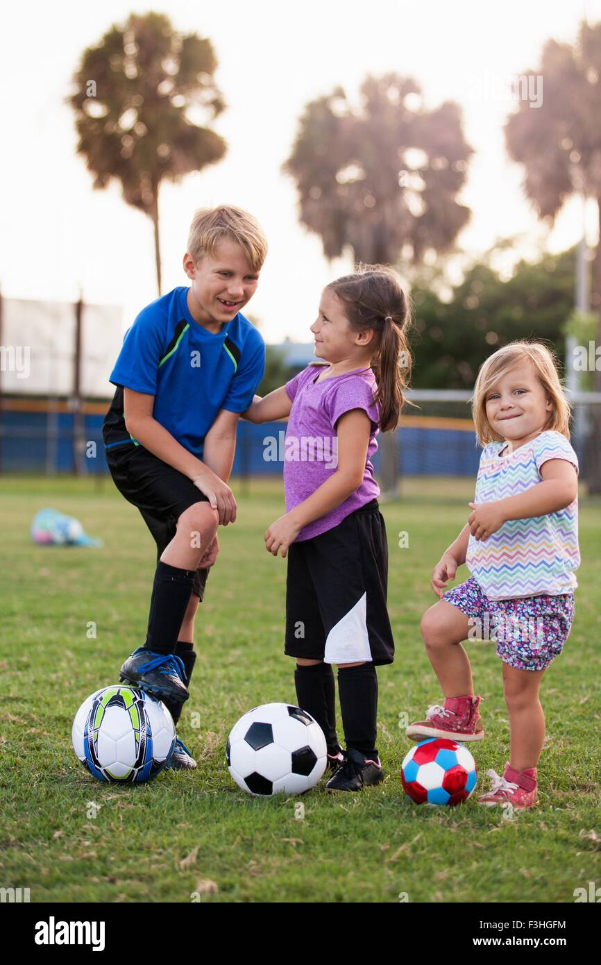 Boy and younger sisters with footballs on practice pitch - Stock Image