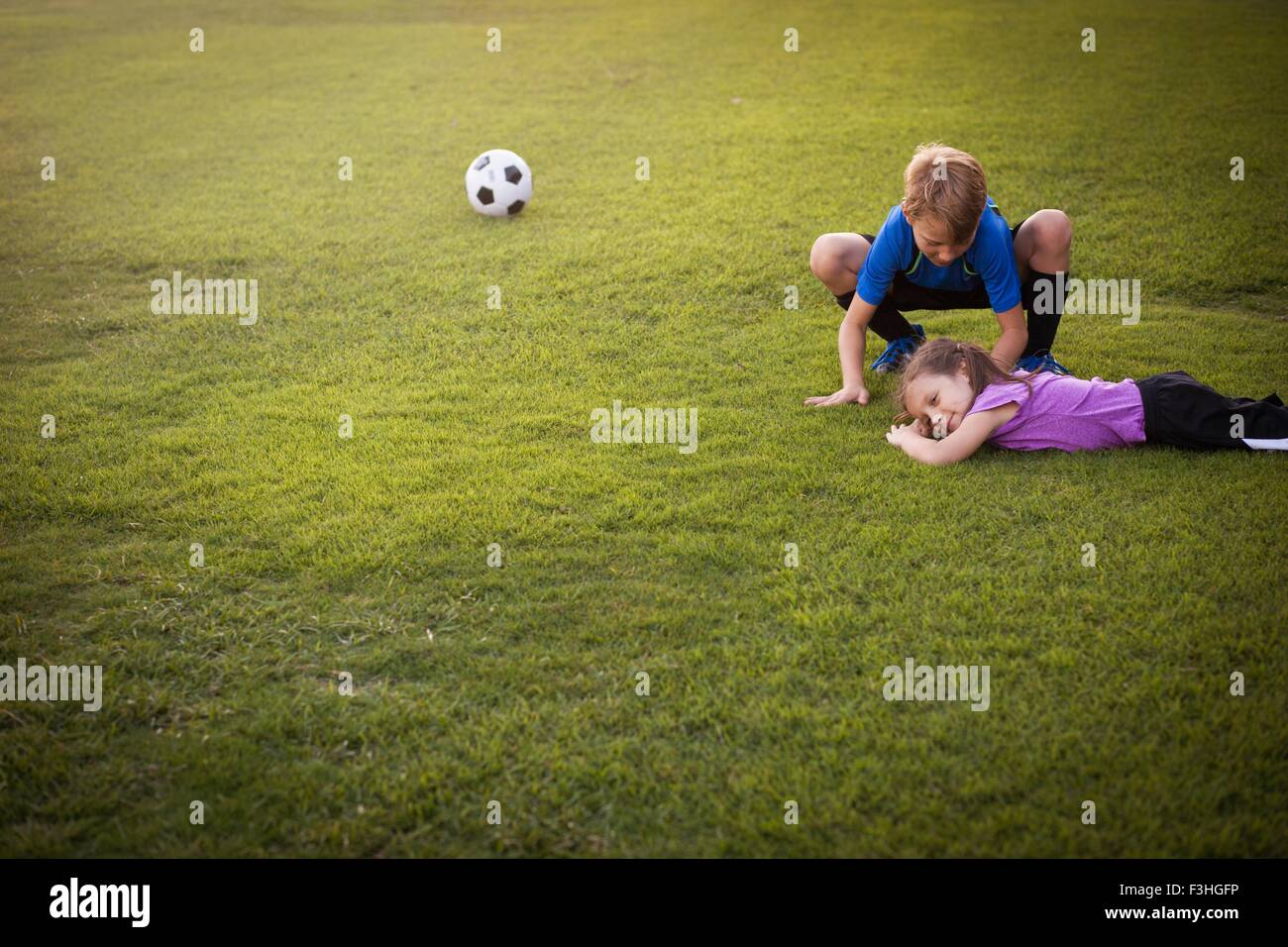 Boy tending injured younger sister on football practice pitch - Stock Image