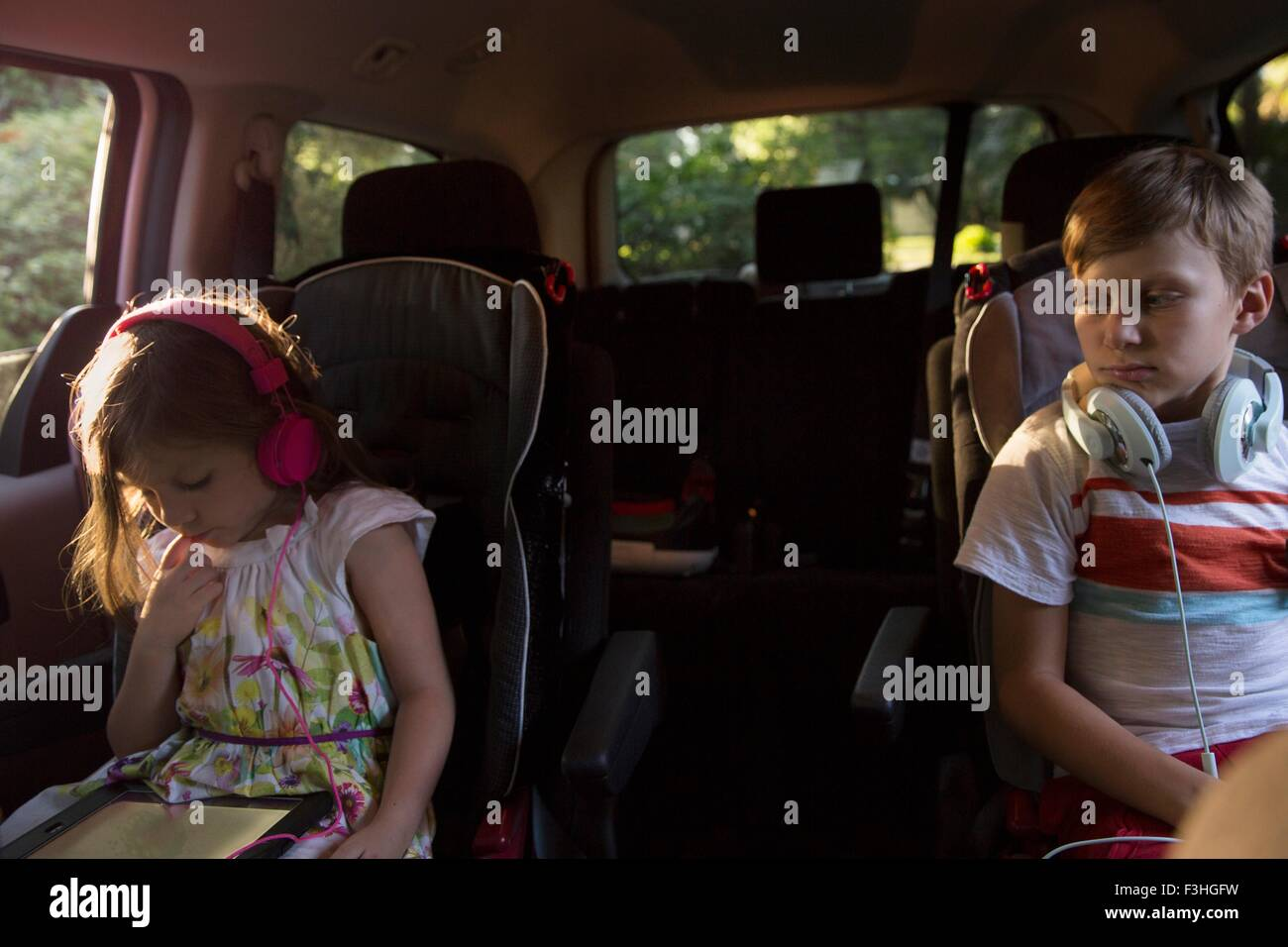 Boy watching younger sister using digital tablet in car back seat - Stock Image