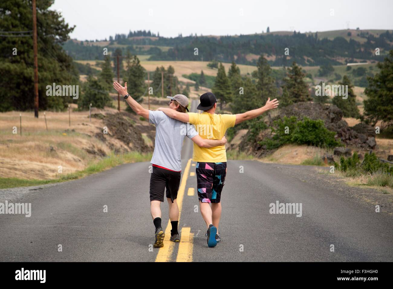 Two men walking along road together, arms raised, appreciating view, rear view - Stock Image