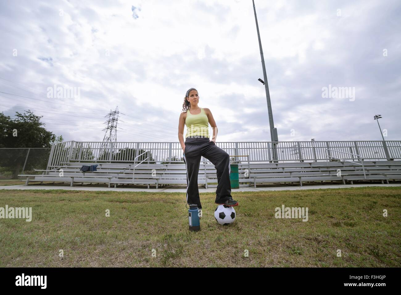 Soccer player stepping on ball in field - Stock Image