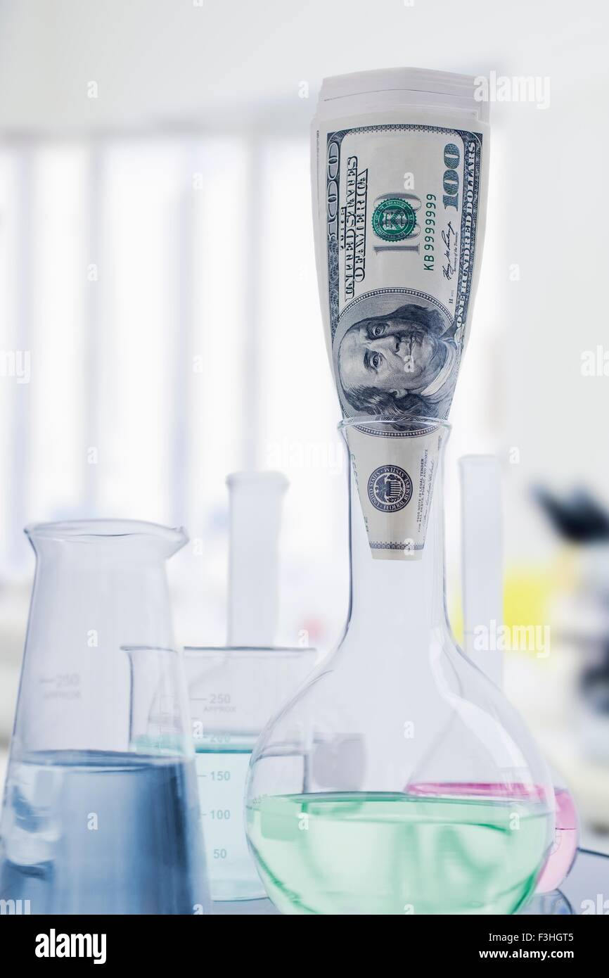 One hundred dollar bill in flat bottomed glass chemistry flask - Stock Image
