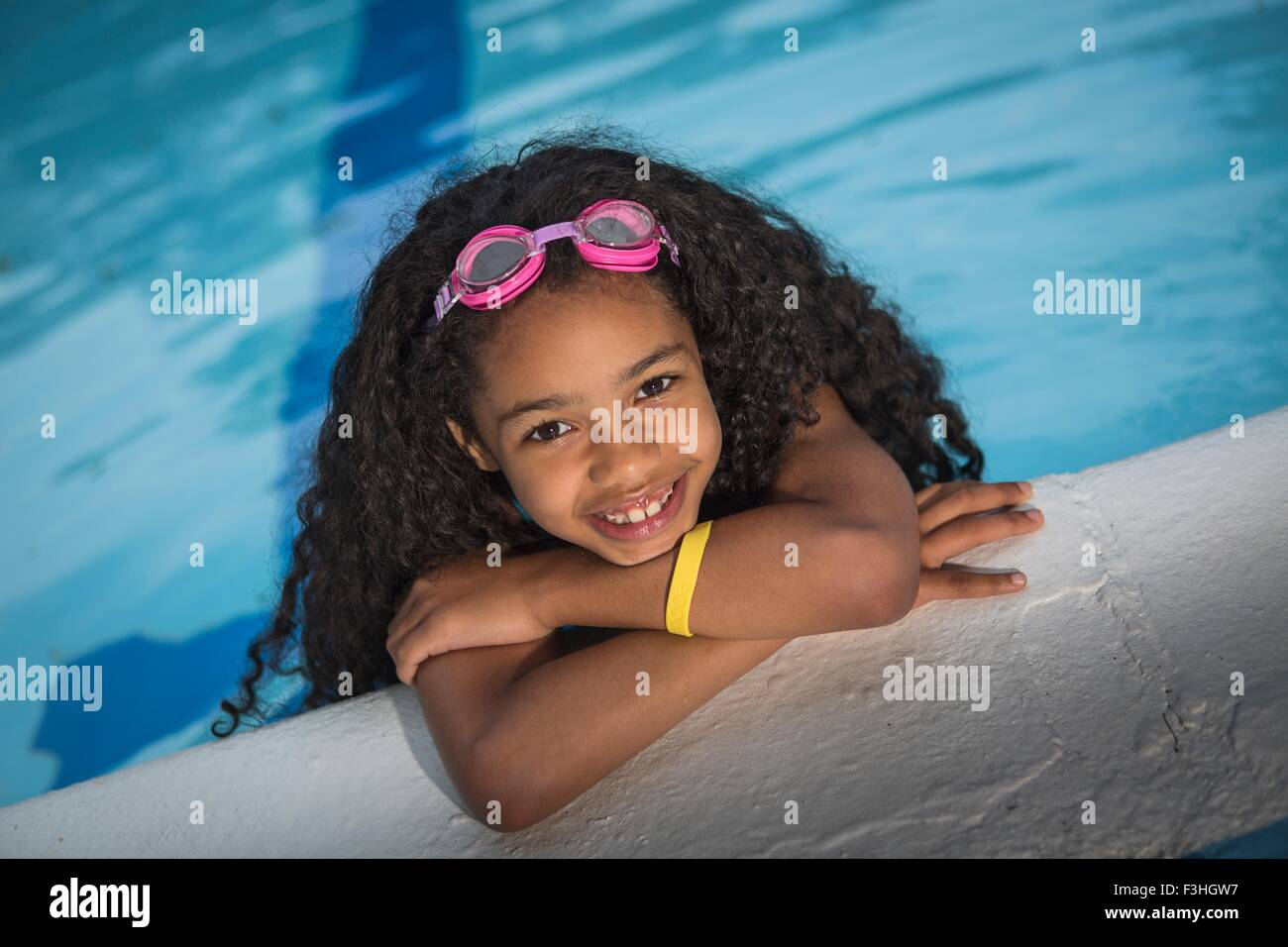 Portrait of girl with curly black hair hanging on edge of swimming pool, looking at camera smiling - Stock Image