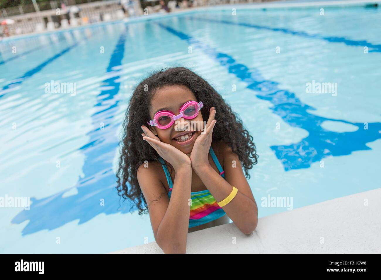 Portrait of girl in swimming pool wearing swimming goggles, looking at camera smiling - Stock Image