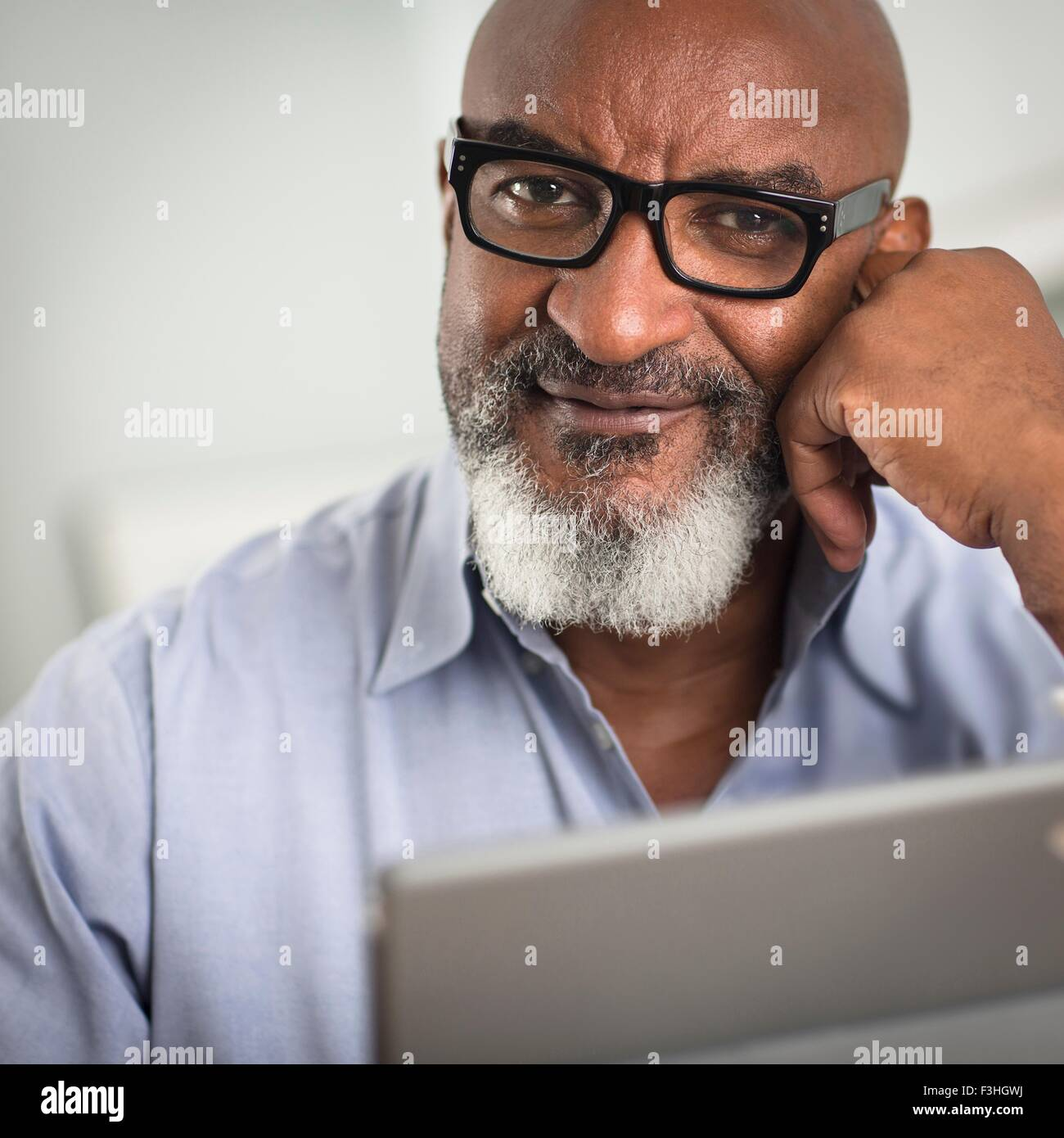 Portrait of mature man with greying beard and glasses, looking at camera smiling - Stock Image
