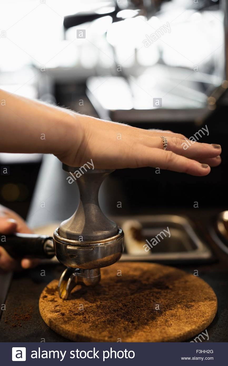 Coffee shop barista removing coffee grounds, close-up - Stock Image
