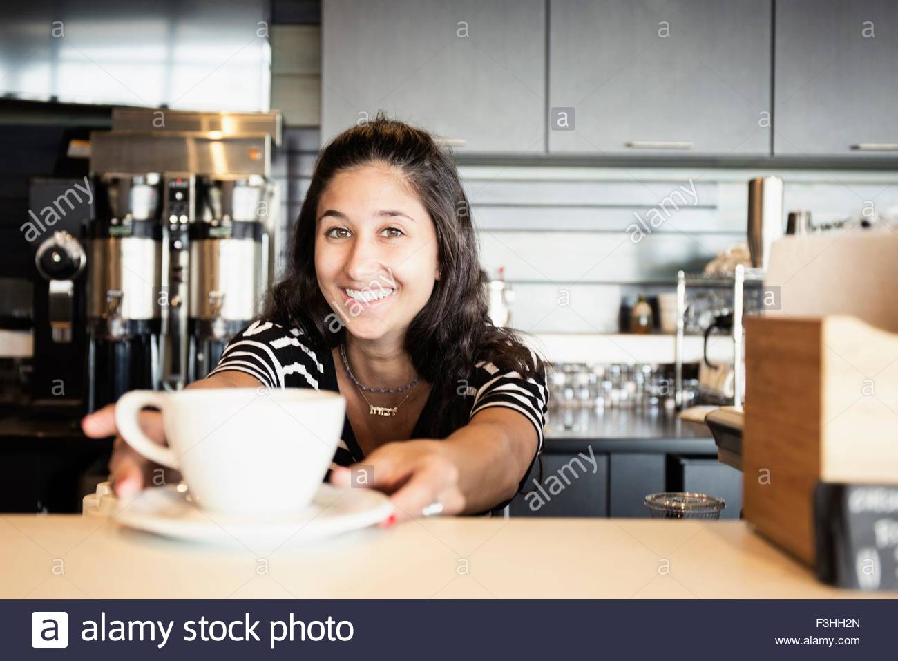 Coffee shop barista serving coffee - Stock Image
