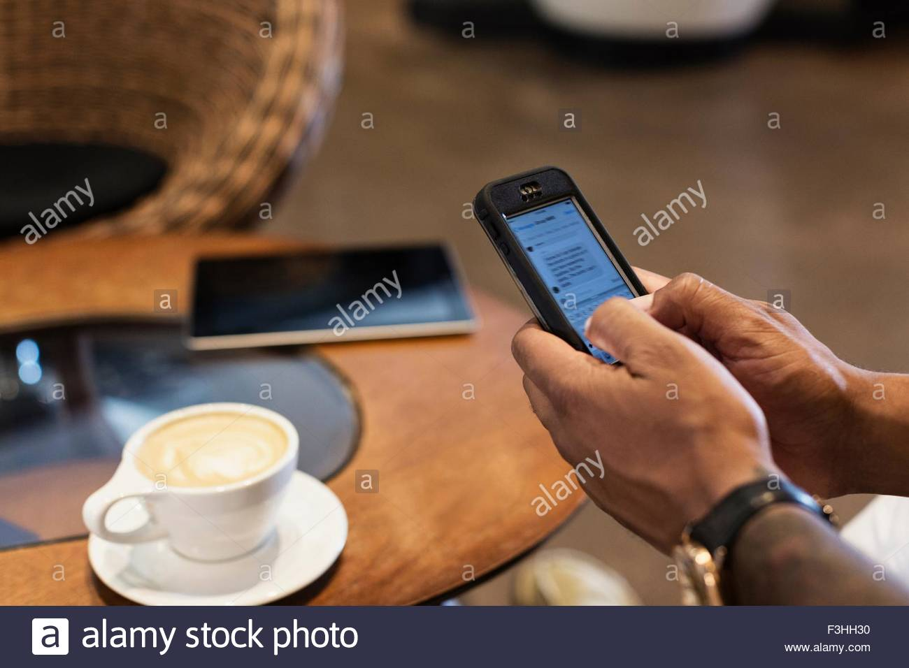 Young man in coffee shop using smartphone, focus on hands - Stock Image