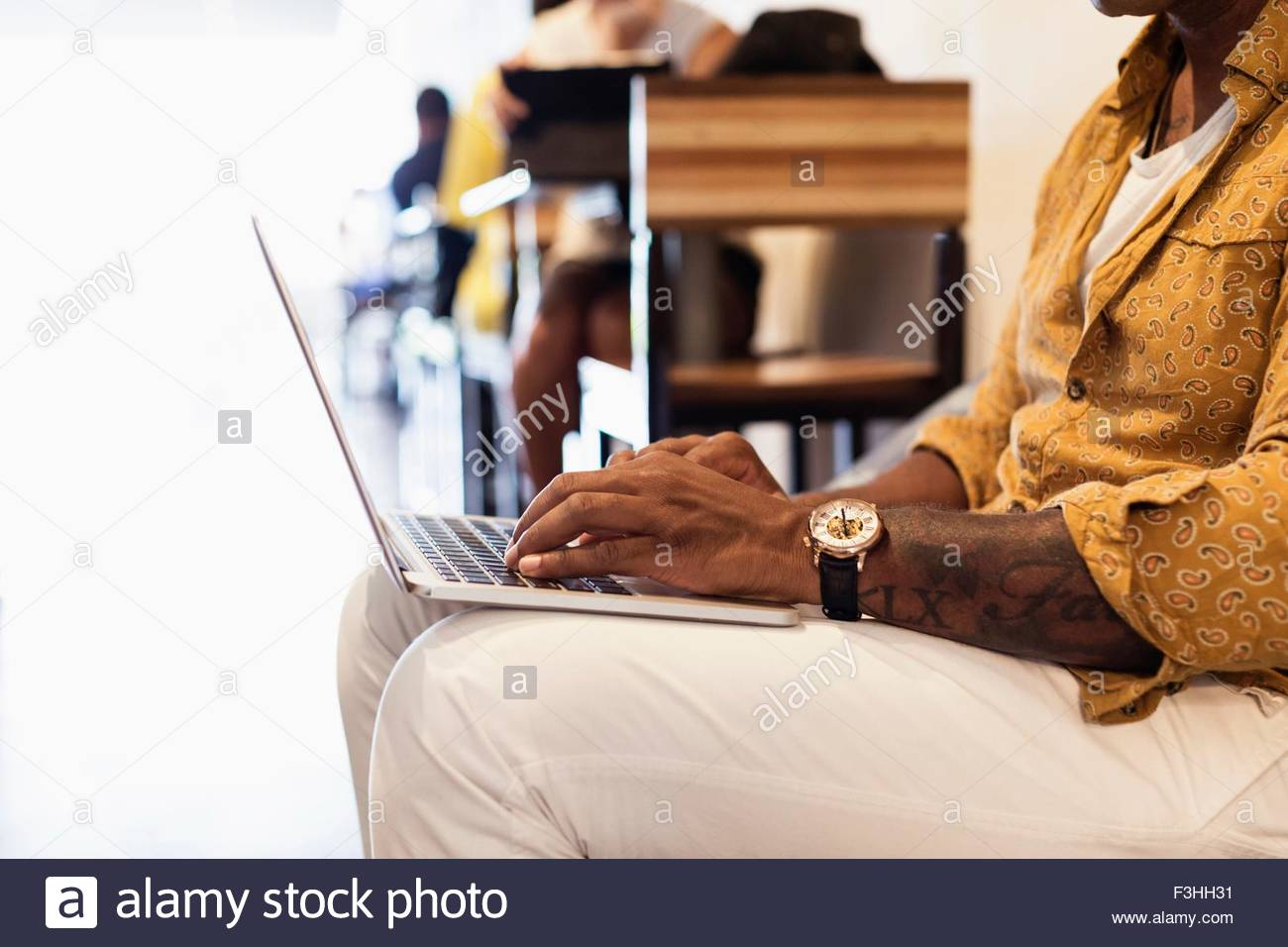 Young man in coffee shop, using laptop, mid section - Stock Image