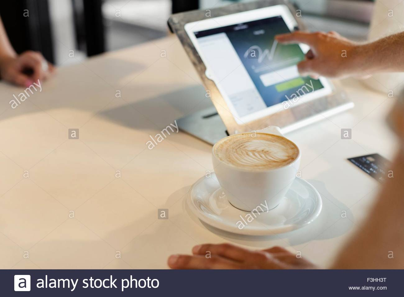 Customer paying for coffee in coffee shop, signing signature on digital transaction technology - Stock Image
