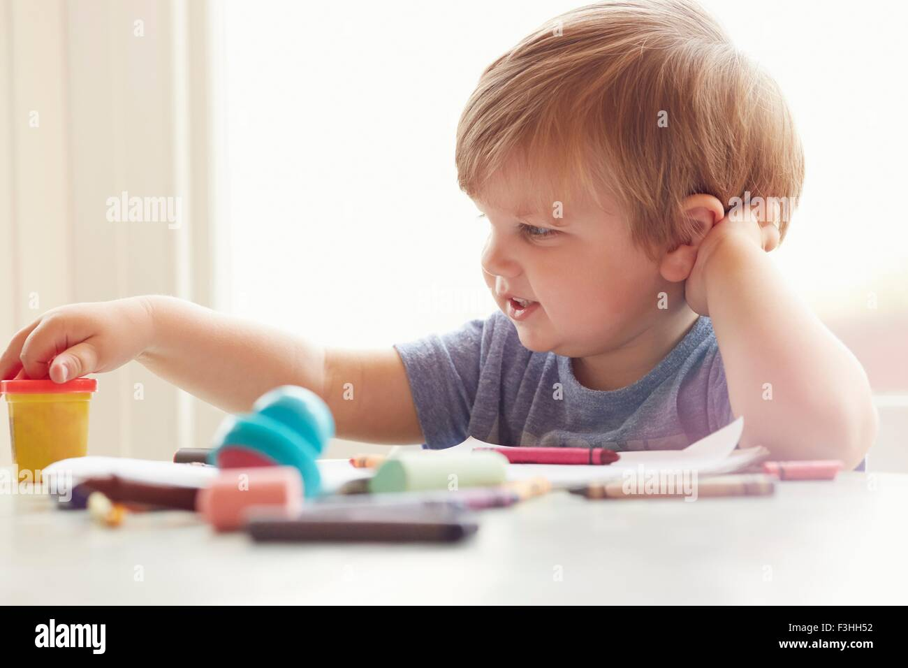 Boy sitting at table leaning on elbow looking at art supplies - Stock Image