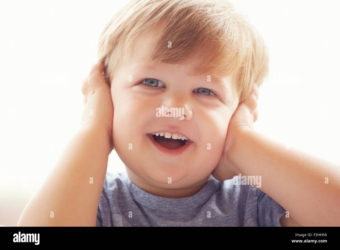 Portrait of young boy covering ears with hands, looking away smiling - Stock Image