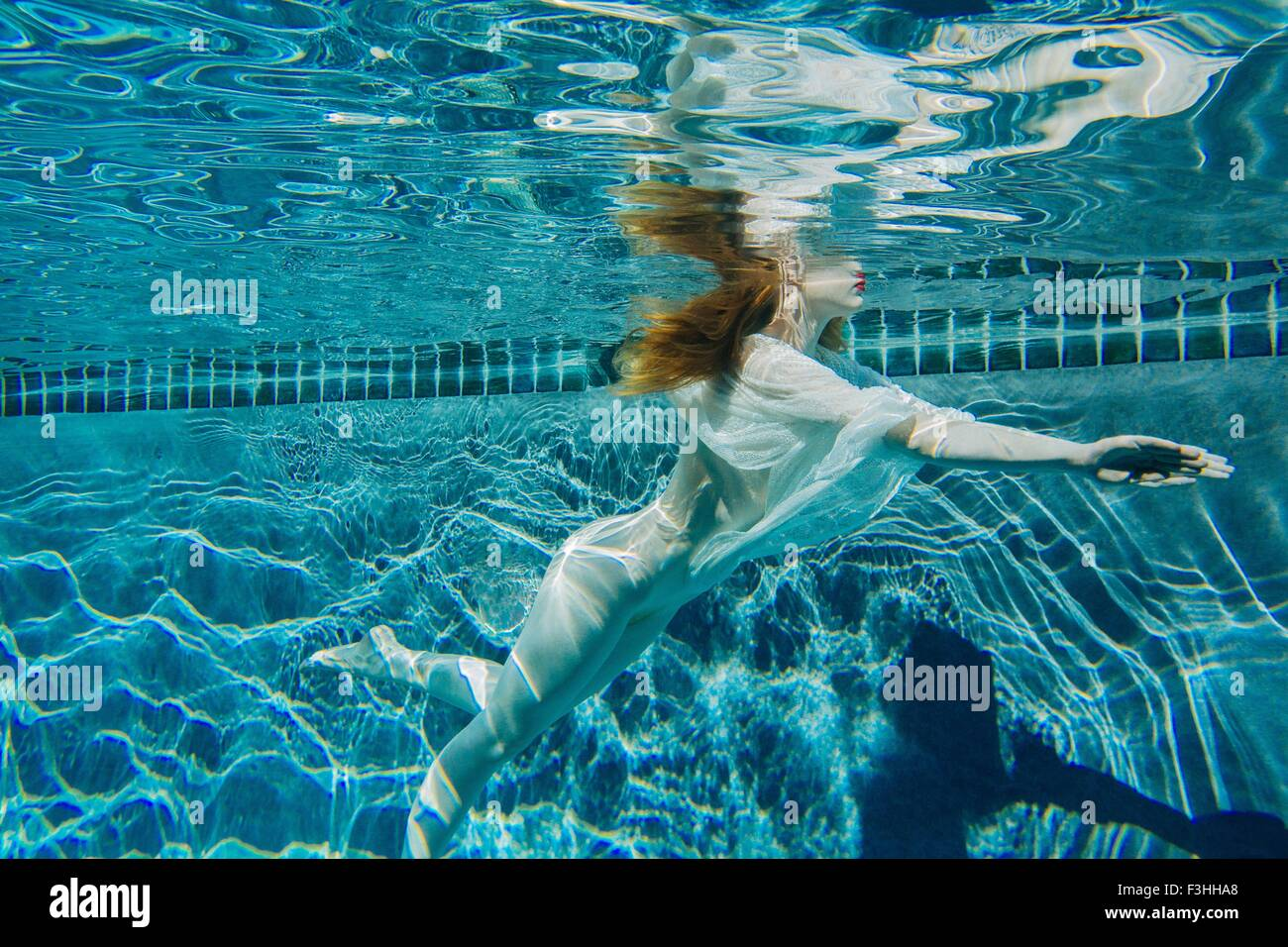 Young Woman Underwater Wearing Thin White Shirt And Pearls