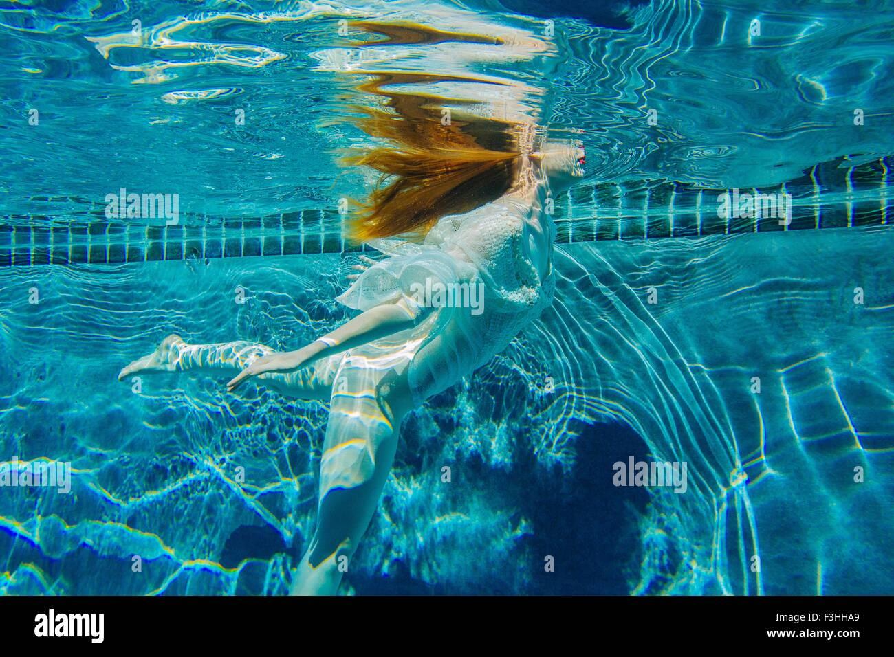 Young woman underwater, wearing thin white shirt - Stock