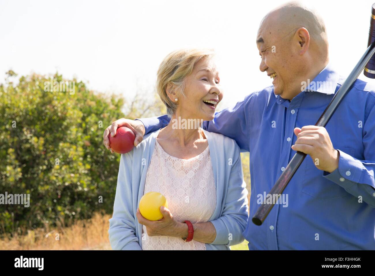 Portrait of senior couple in park, holding croquet mallet and balls - Stock Image