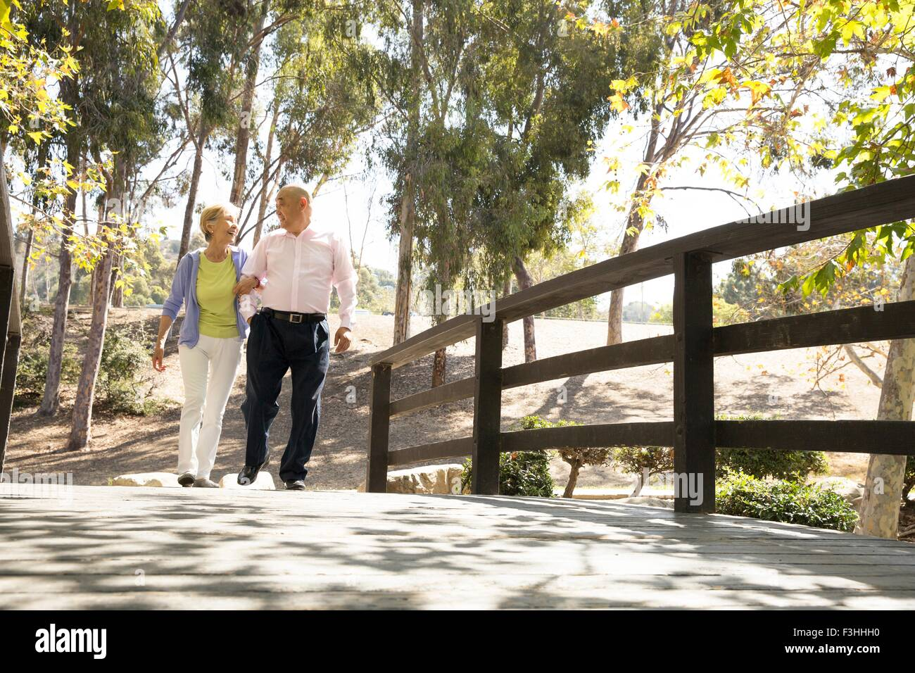 Senior couple walking arm in arm across footbridge - Stock Image