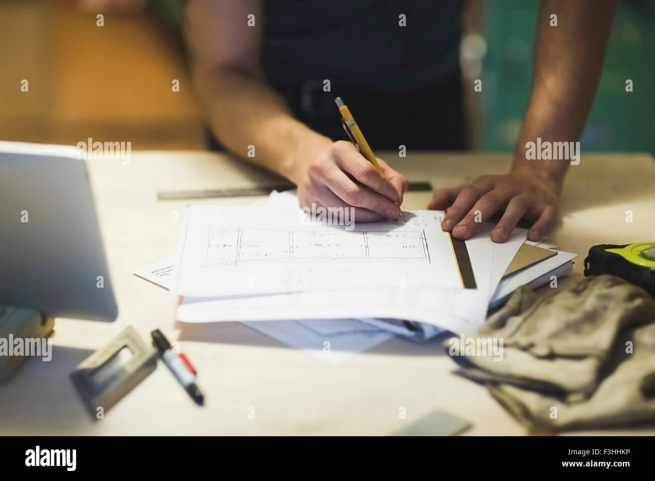 Cropped view of young mans hands writing on blueprint - Stock Image
