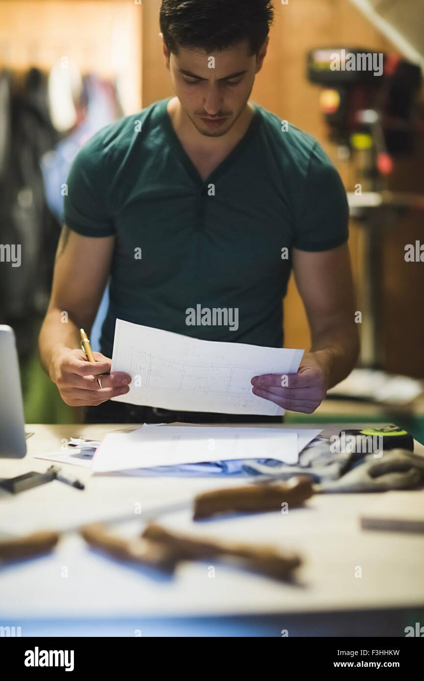 Young man holding paper work, looking down - Stock Image