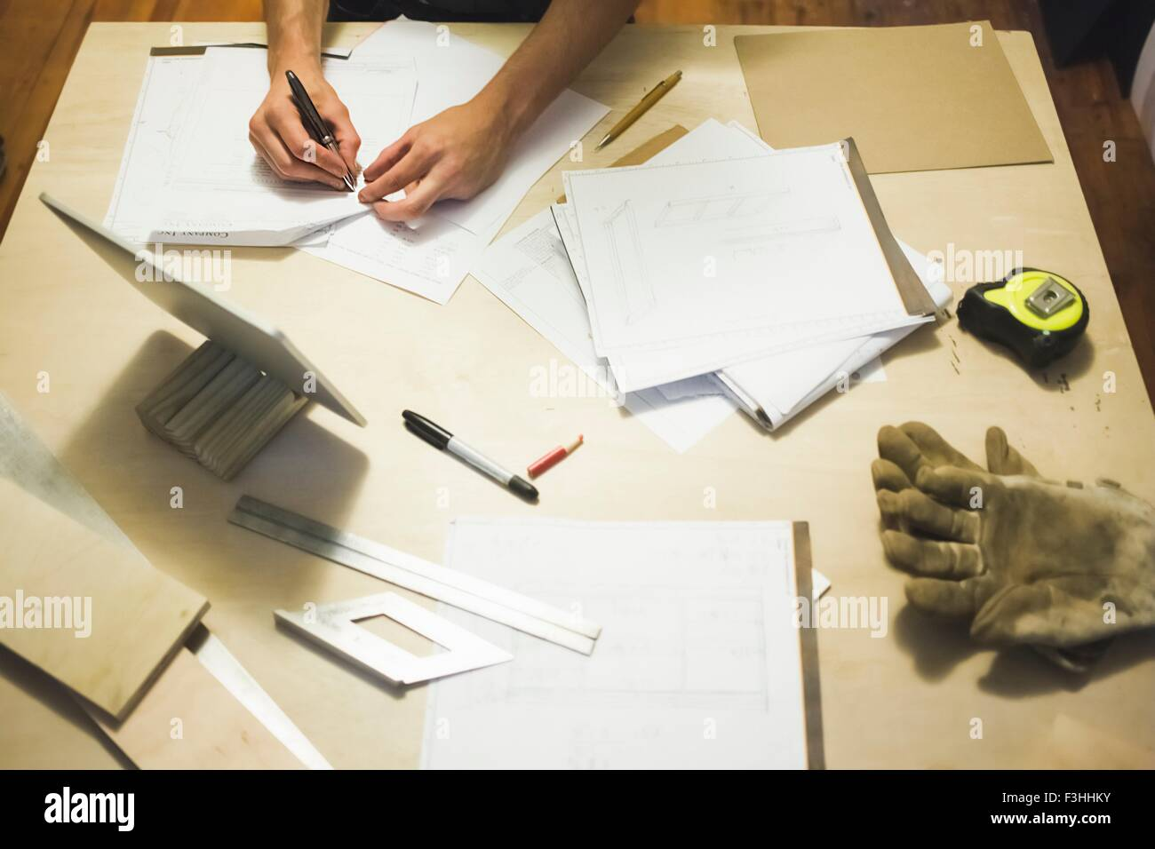 High angle view of desk and young man's hands writing - Stock Image