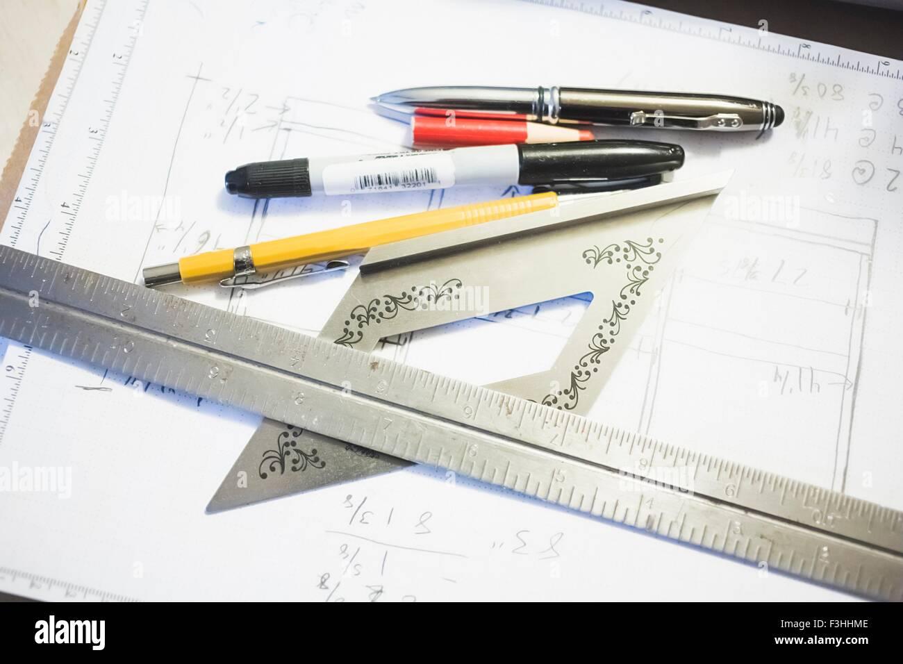 High angle view of stationary and metal ruler on blueprint - Stock Image