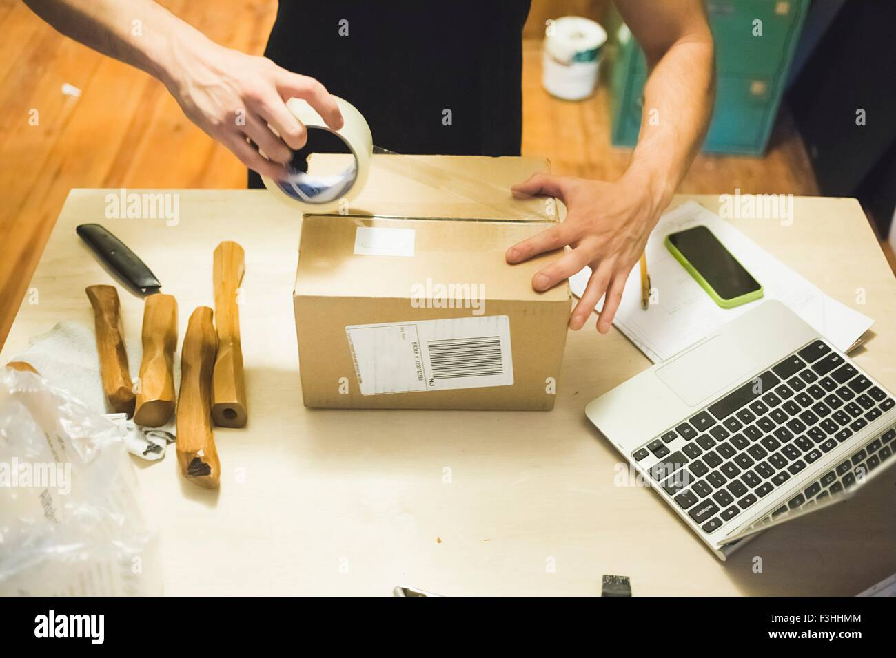 High angle view of young mans hands using sticking tape to prepare package for delivery - Stock Image