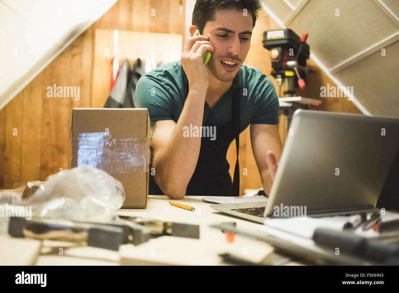 Young man in workshop sitting at desk talking on telephone looking at laptop - Stock Image