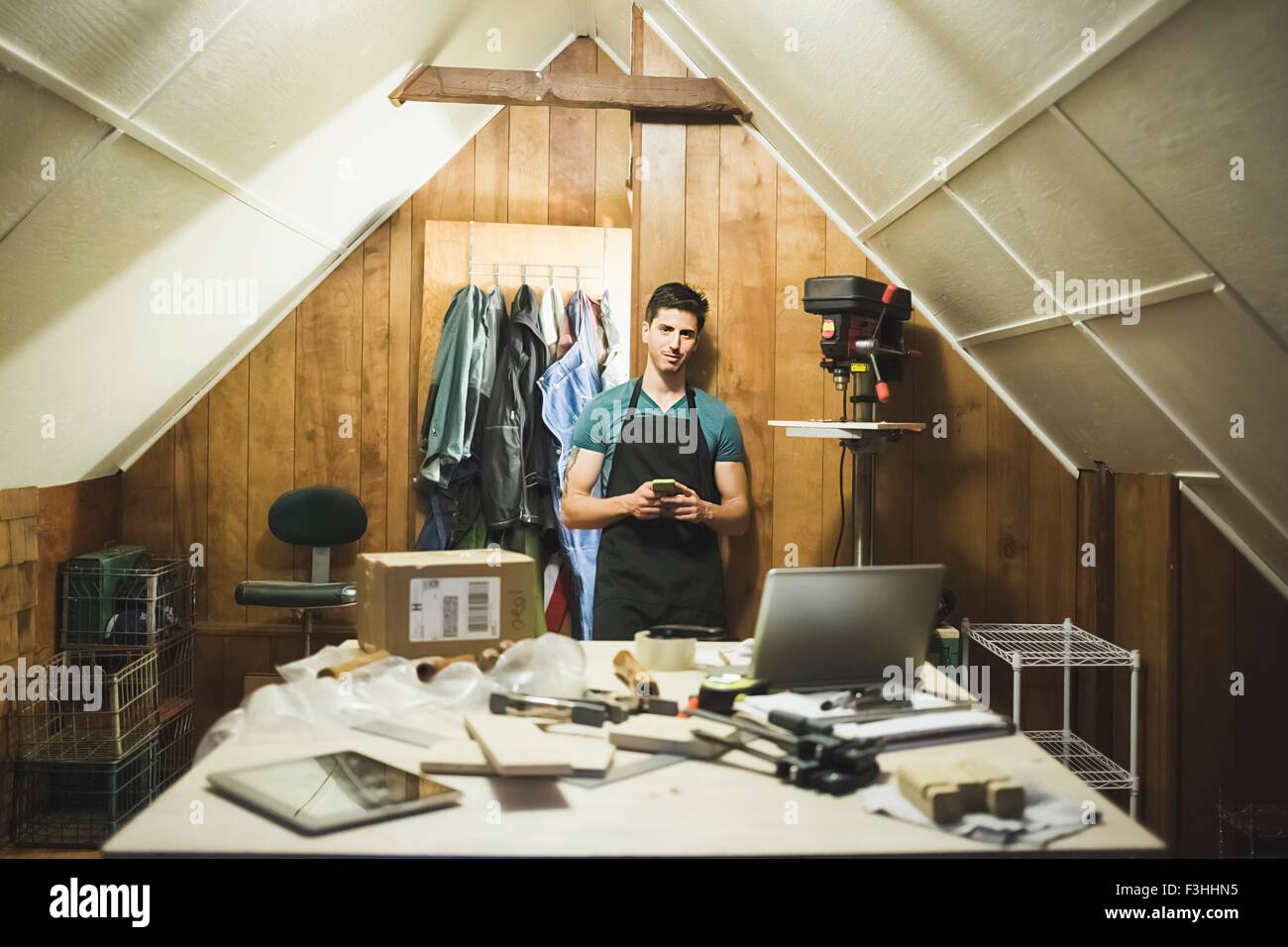 Young man wearing apron standing behind desk in workshop, looking at camera - Stock Image