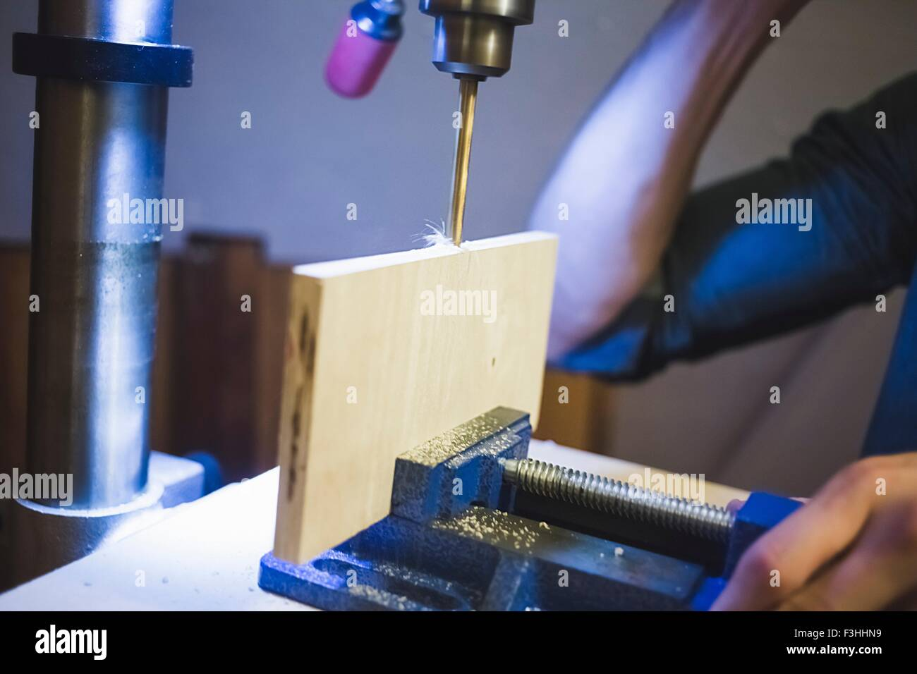 Cropped view of young mans hands operating drill on wood in clamp - Stock Image