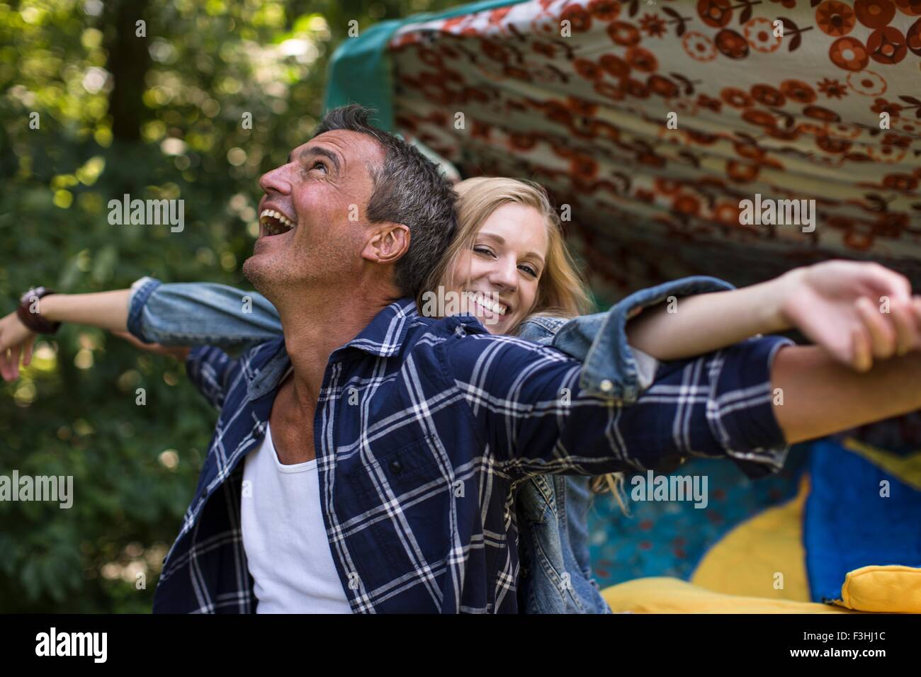 Mature man and girlfriend fooling around whilst camping - Stock Image