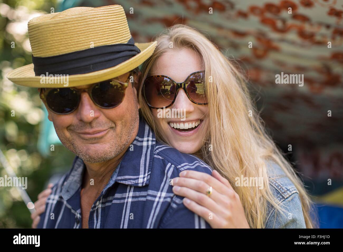 Portrait of mature man and girlfriend wearing sunglasses - Stock Image