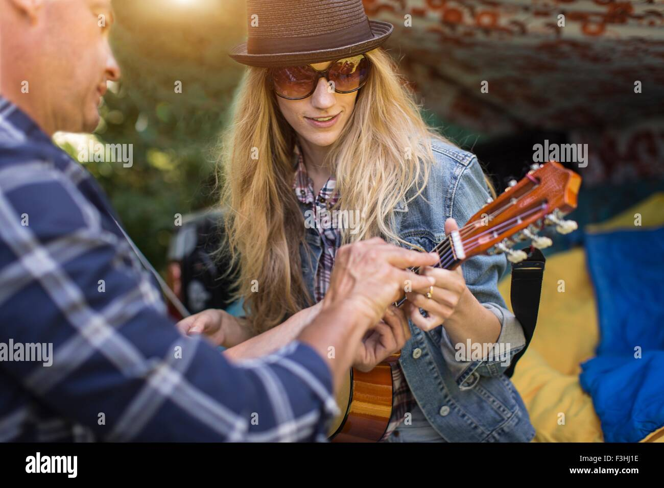 Mature man showing girlfriend how to play ukulele whilst camping in pick up boot - Stock Image