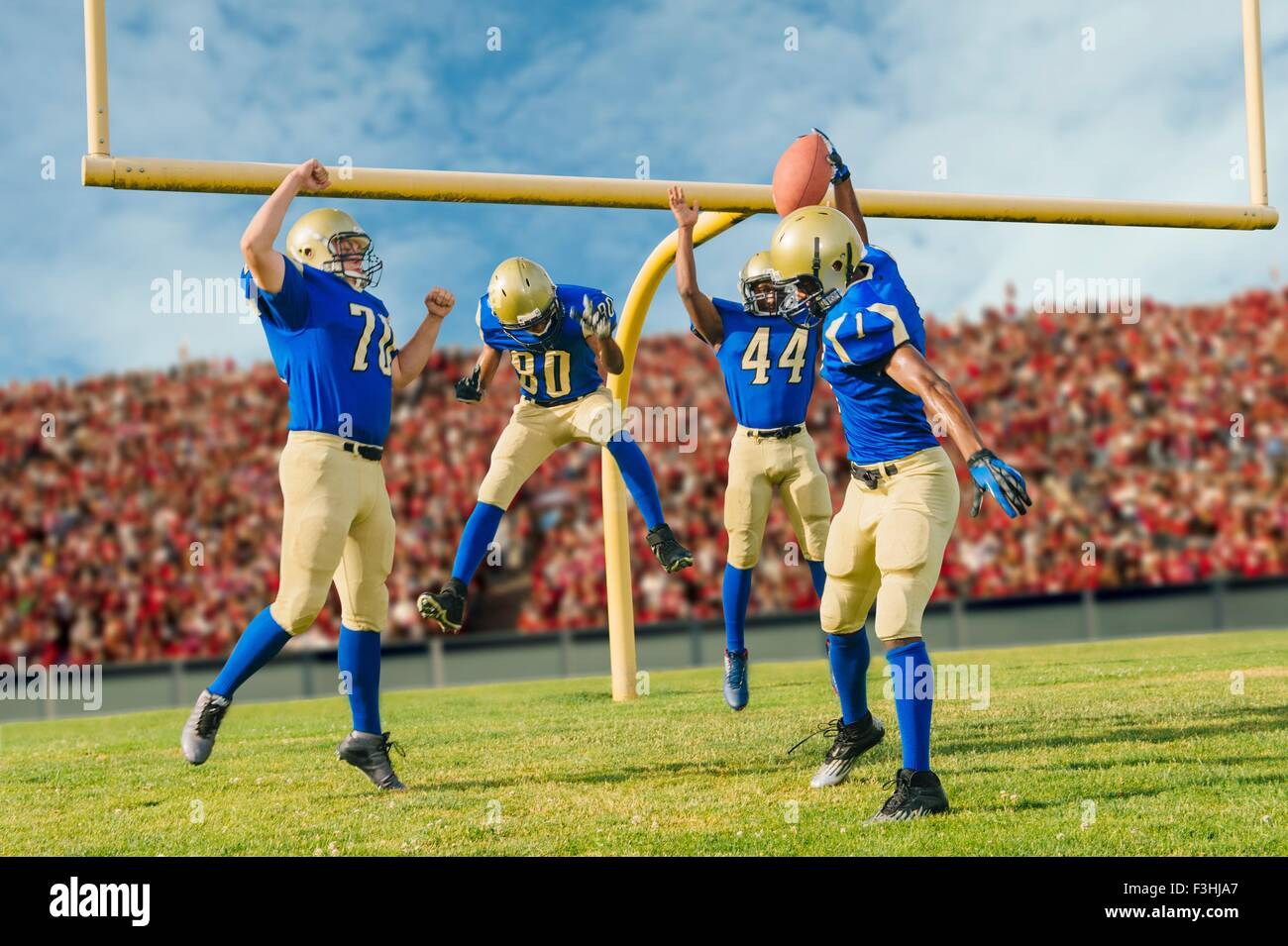 Team of teenage and adult American footballers playing in stadium next to field goal Stock Photo
