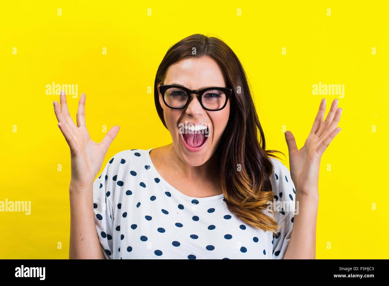 Portrait of young woman with eyeglasses, screaming - Stock Image