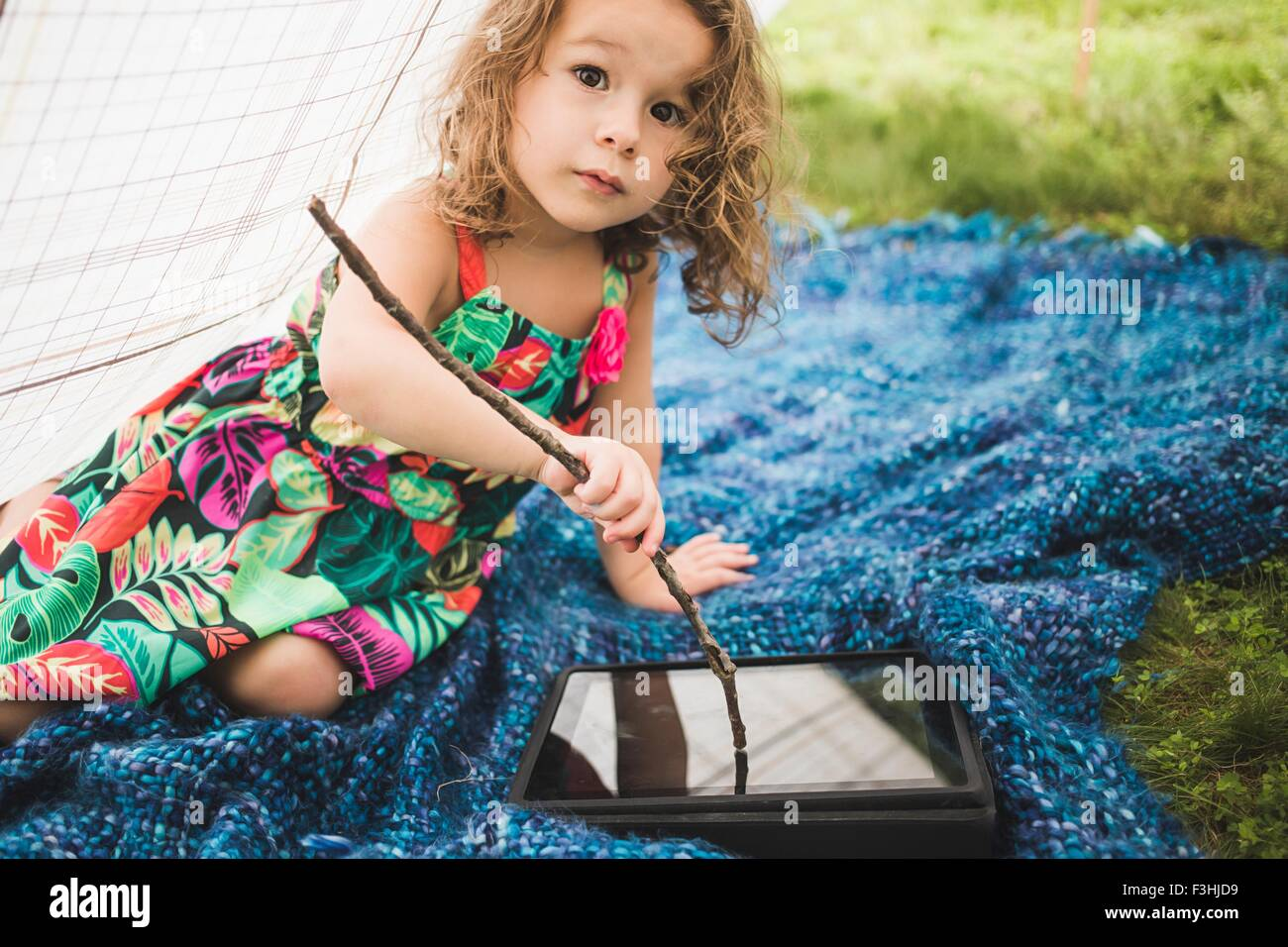 Girl in homemade garden tent using twig on digital tablet screen - Stock Image