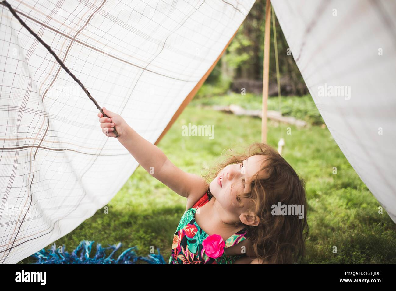 Girl poking homemade garden tent with twig - Stock Image