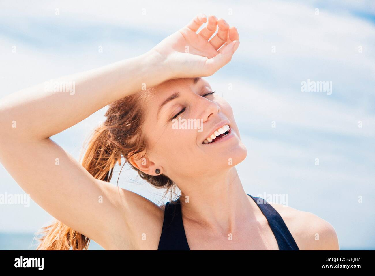 Mid adult woman on beach, arm resting on head - Stock Image