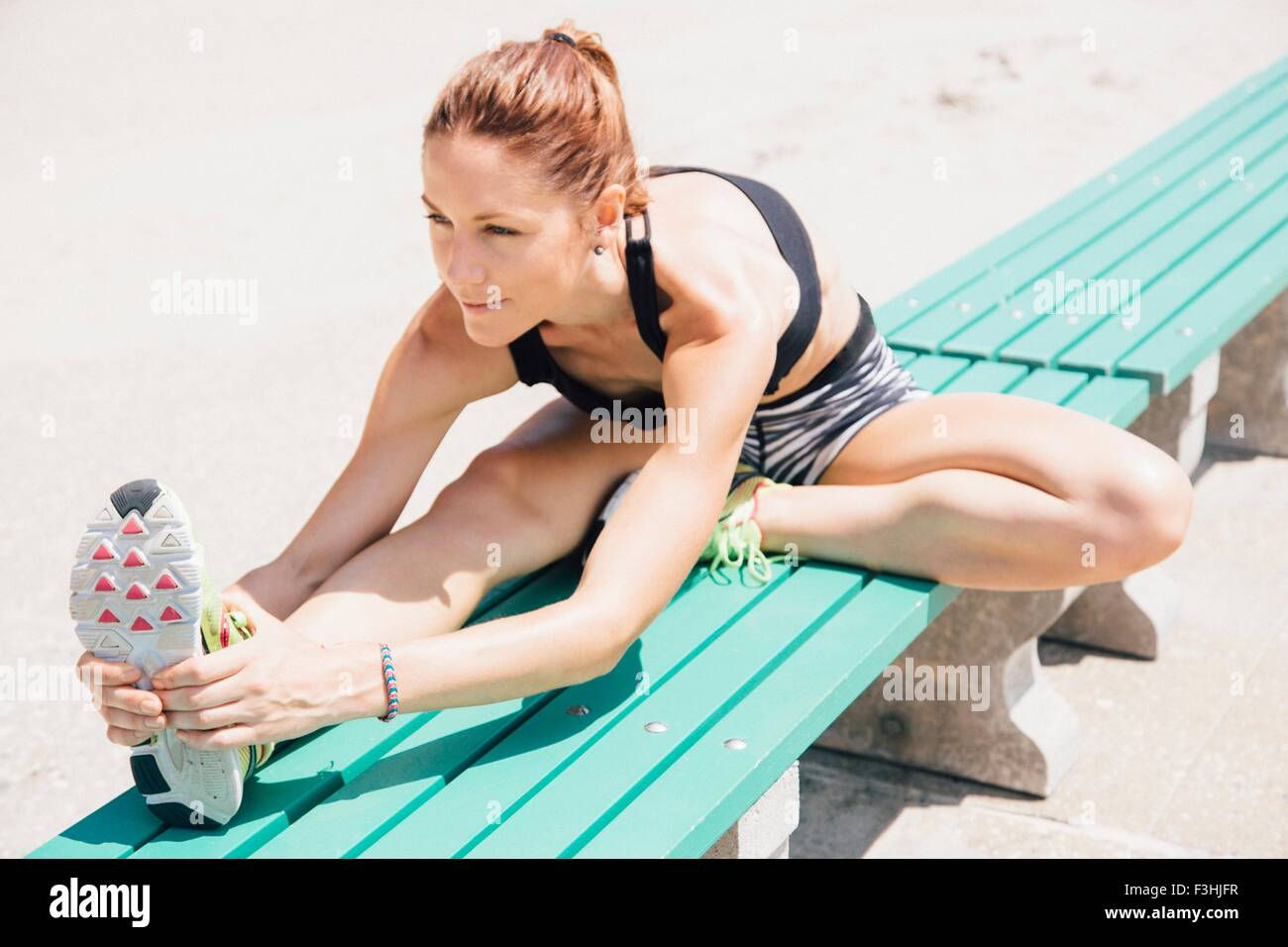 Mid adult woman sitting on bench, stretching - Stock Image