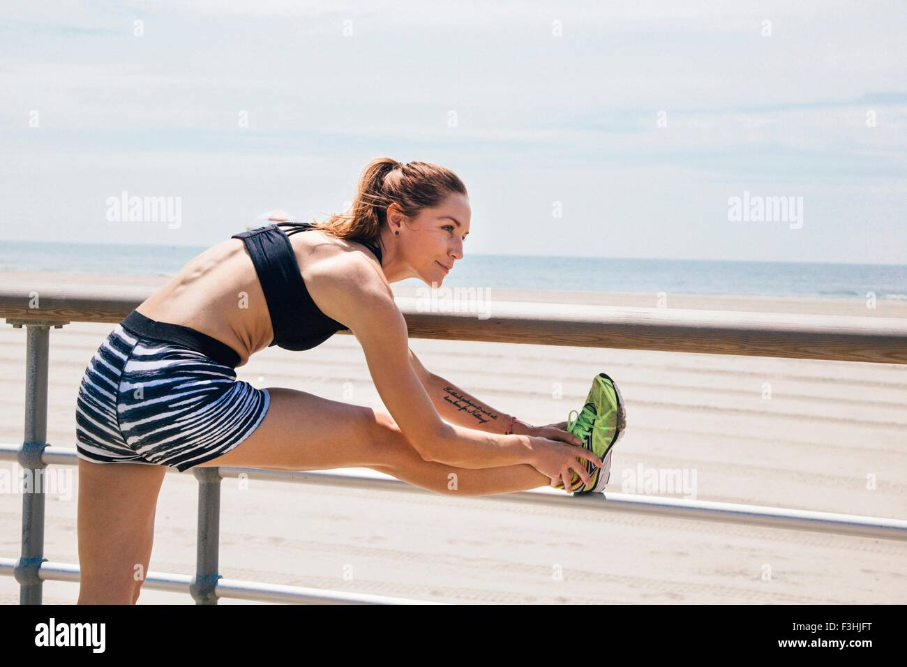 Mid adult woman standing by beach, stretching against railings - Stock Image