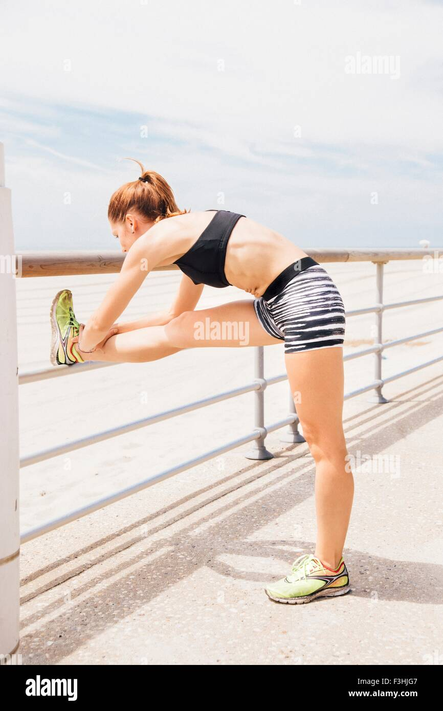 Mid adult woman standing beside beach, stretching against railings, rear view - Stock Image
