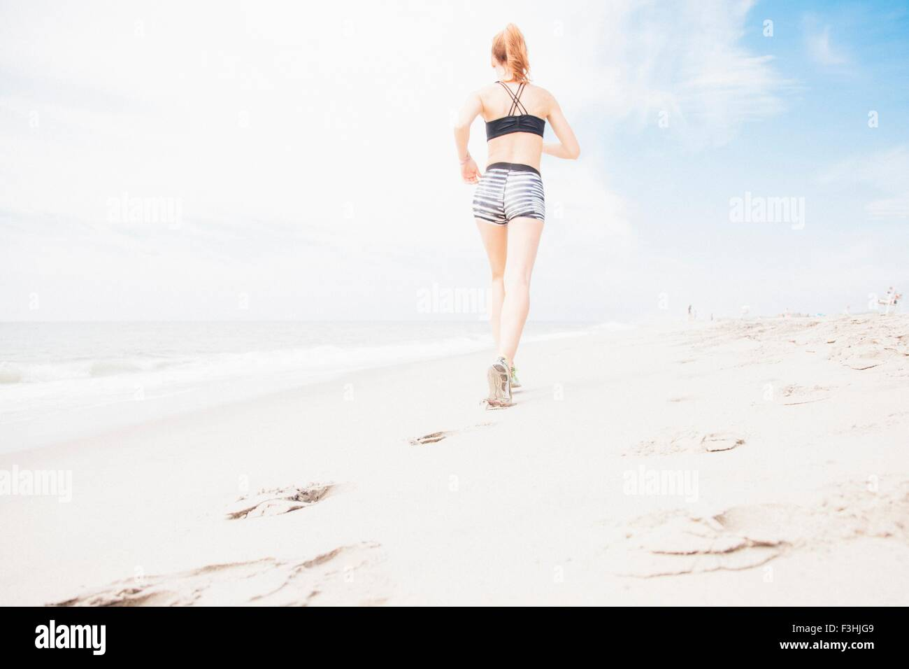 Mid adult woman power walking on beach, rear view, low angle view - Stock Image