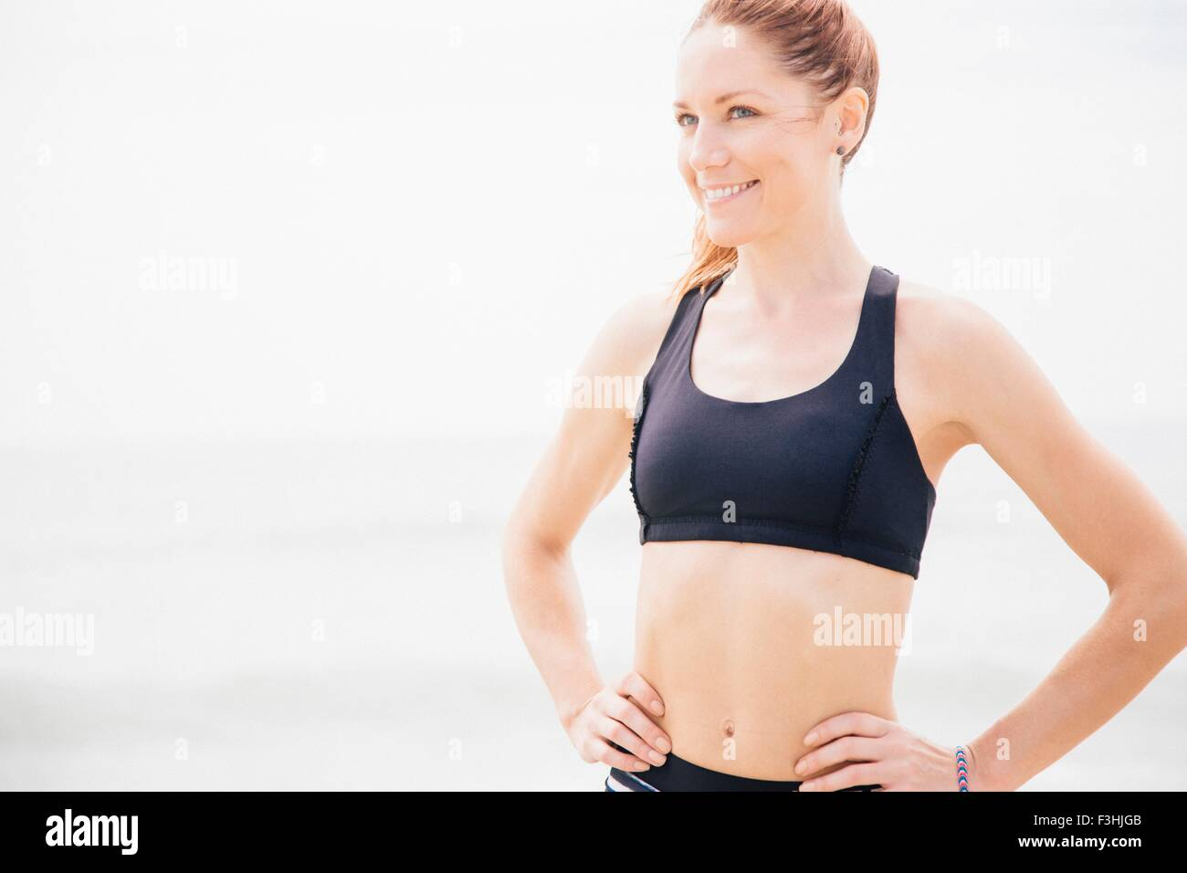Portrait of mid adult woman standing on beach, hands on hips - Stock Image