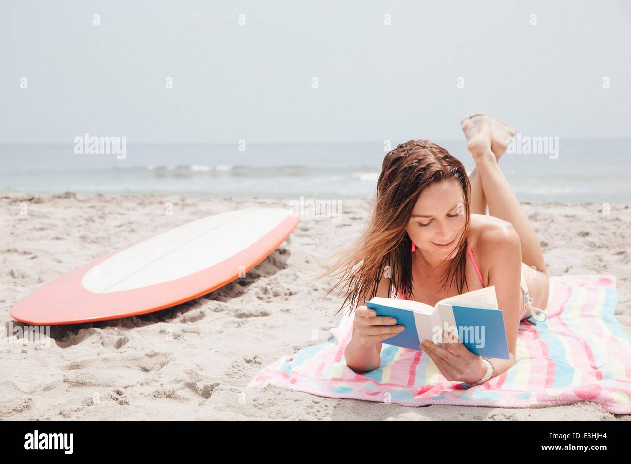 Mid adult woman lying on beach, reading book - Stock Image