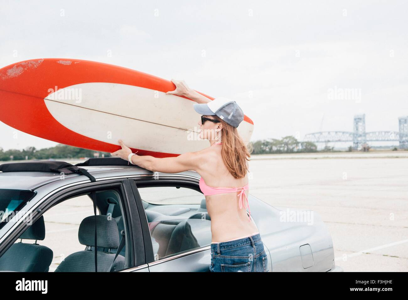 Mid adult woman at beach, removing surfboard from car roof Stock Photo