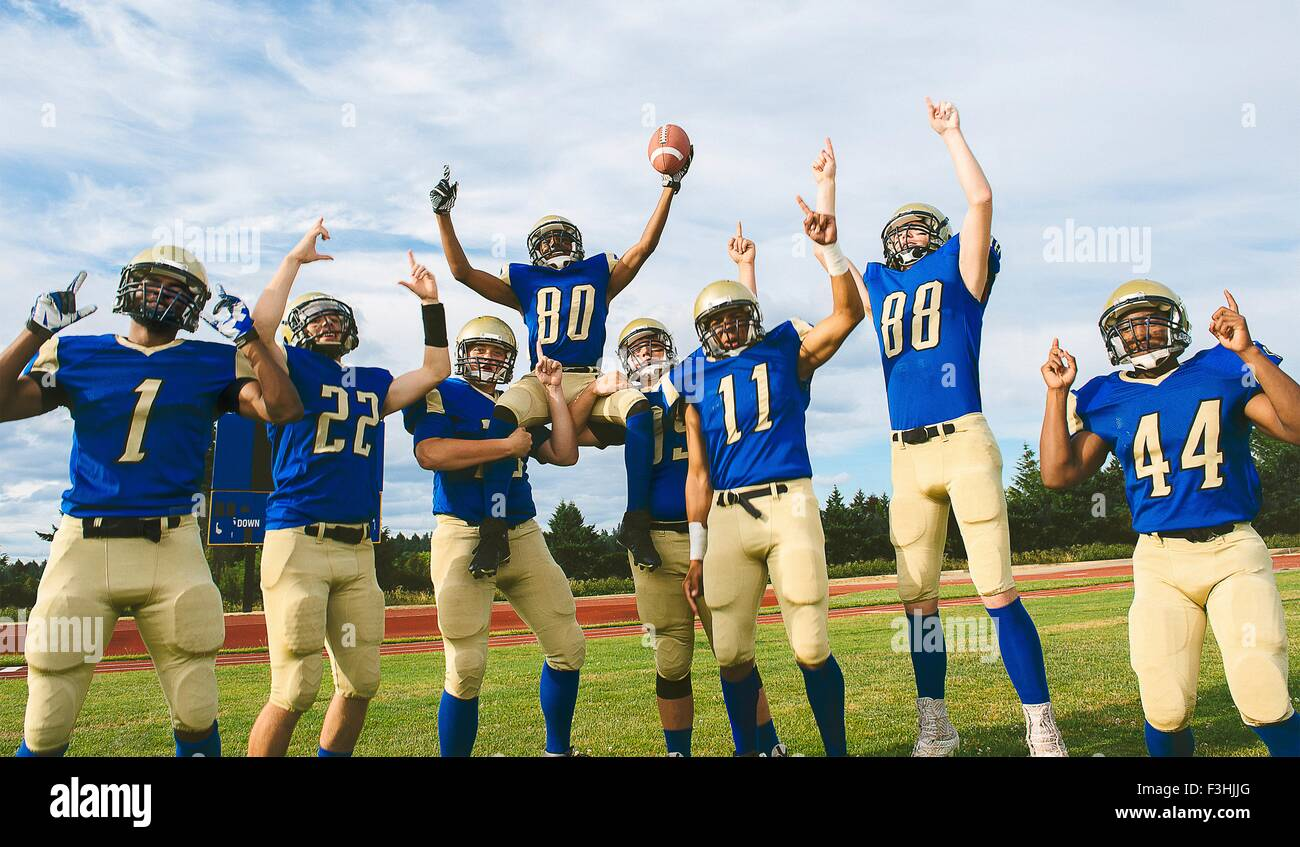 Teenage and young male American football team celebrating on soccer pitch - Stock Image