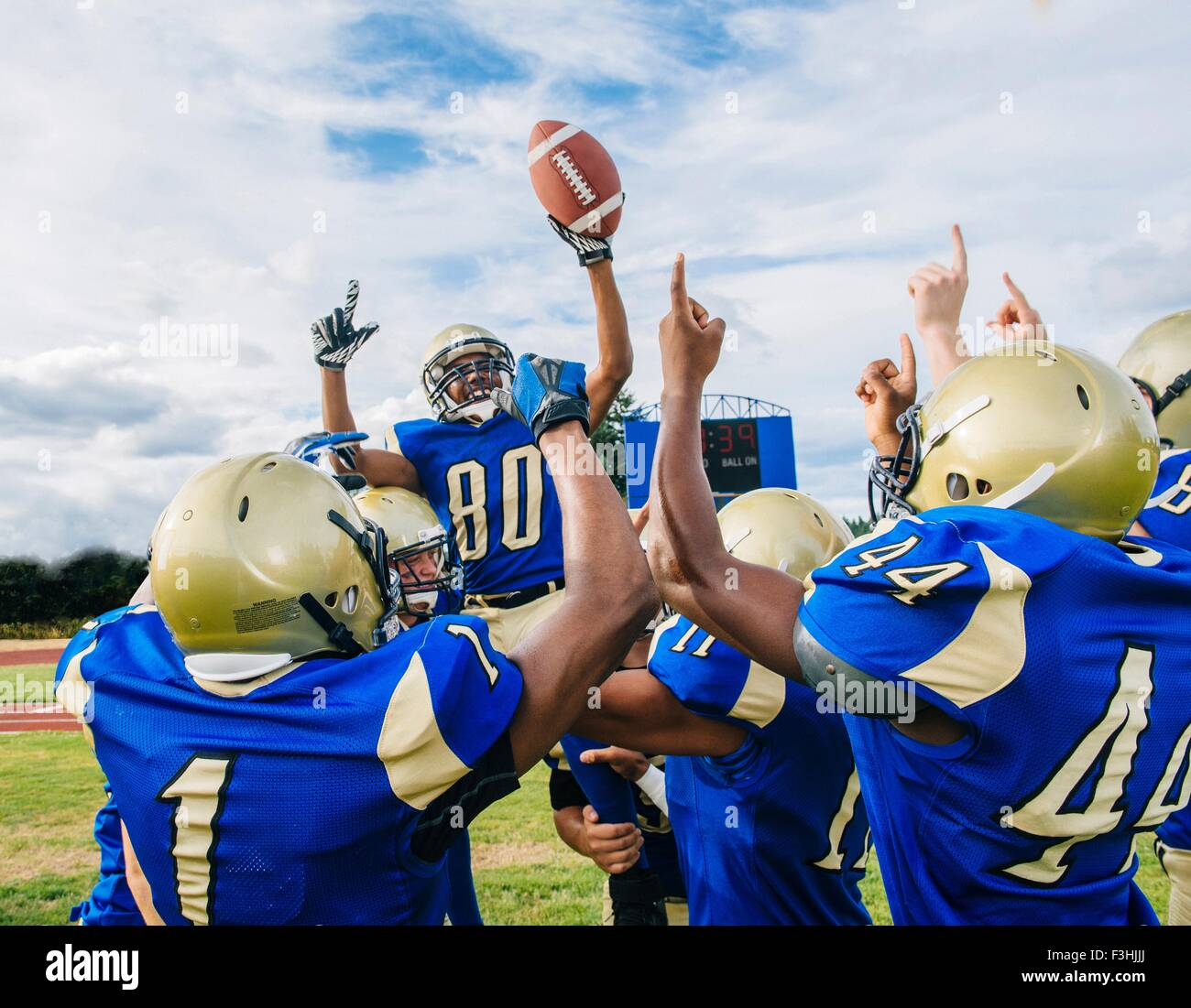 Teenage and young male American football team celebrating victory on soccer pitch - Stock Image