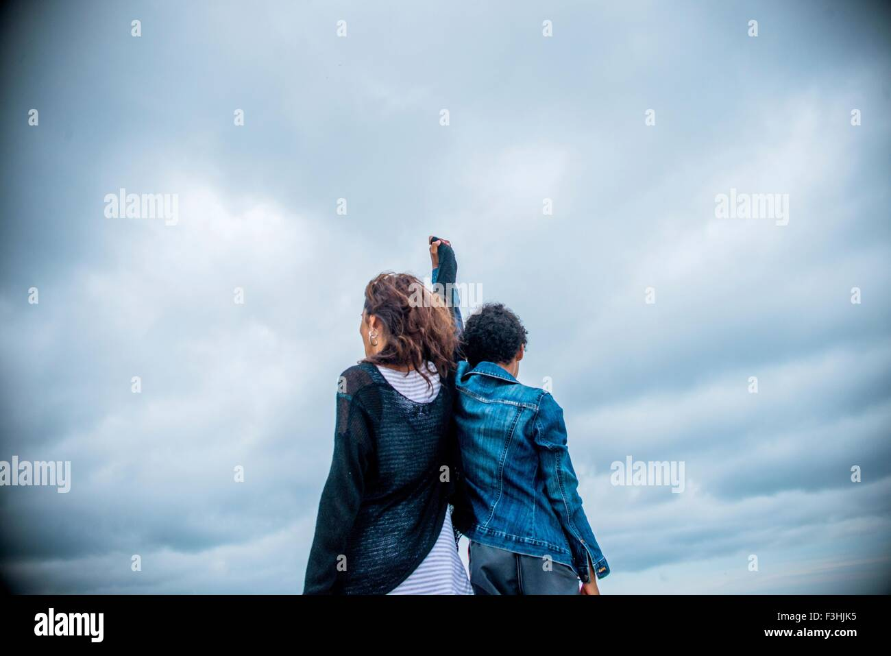 Rear view of mature woman and son shoulder to shoulder against overcast sky - Stock Image