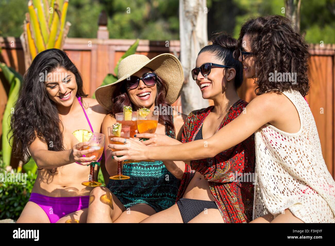 Four adult sisters toasting with cocktails at garden party - Stock Image