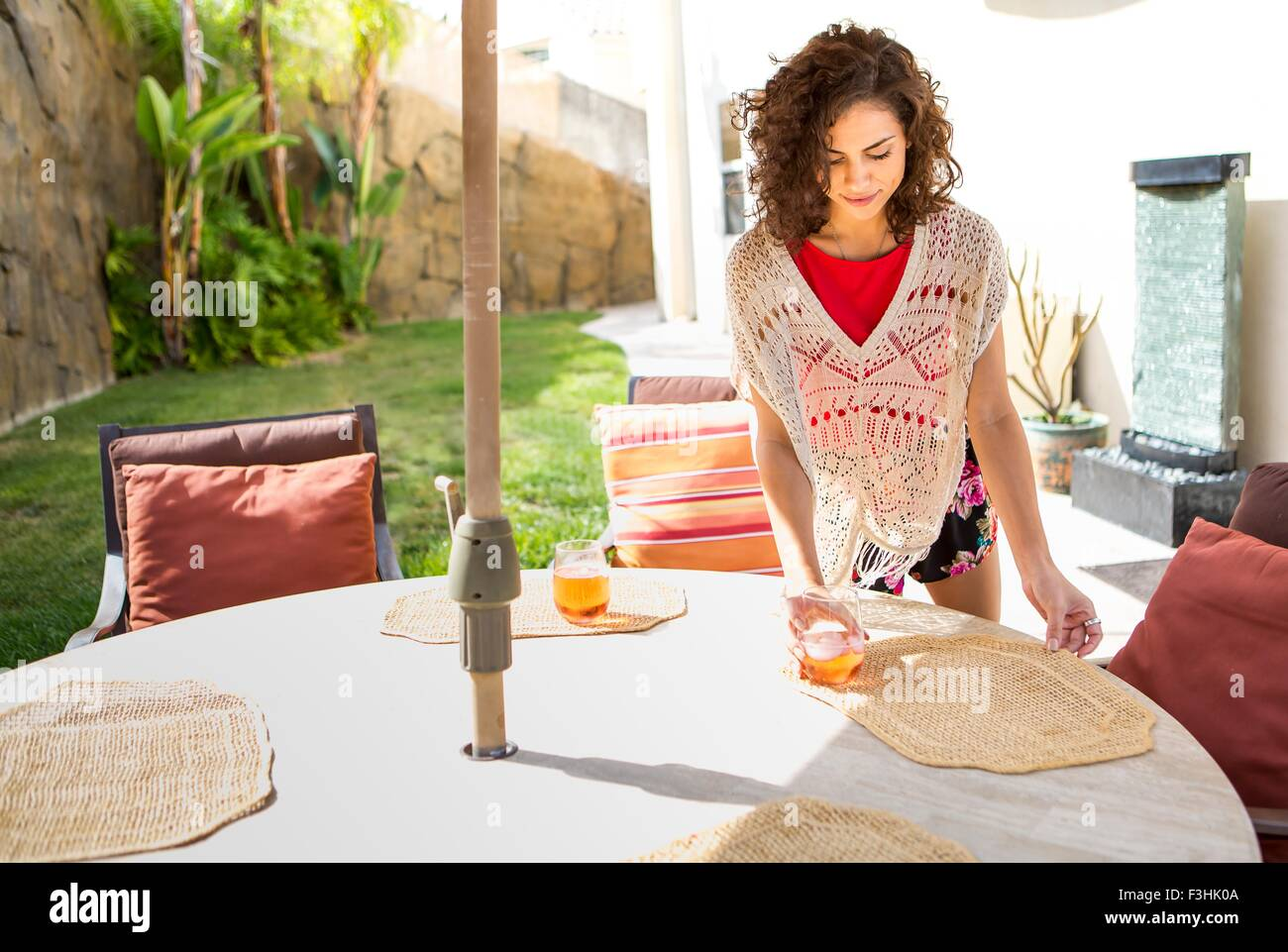 Young woman laying placemats on patio table Stock Photo