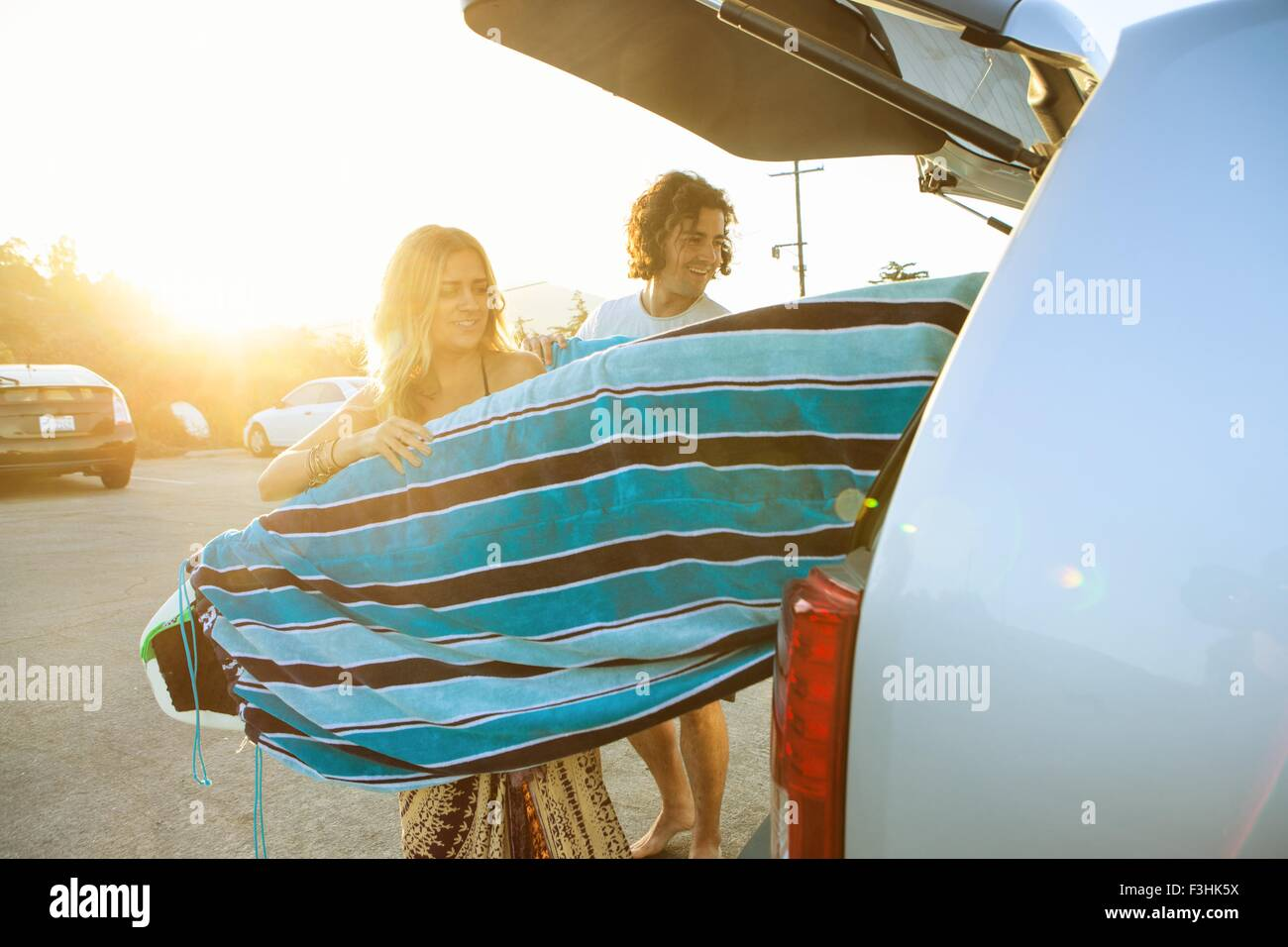Couple taking surfboards from boot of car - Stock Image